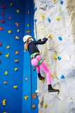 Athlete girl is climbing park on blue wall Royalty Free Stock Photos