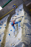 Athlete girl is climbing in sport park on wall Stock Photography