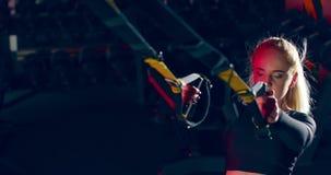 Athlete girl doing pull-ups on trx cables in sports gym `premium gym`. Ukraine Lviv 15.03.2020