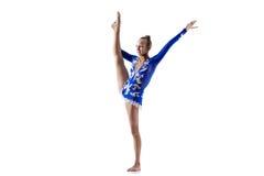 Athlete girl doing standing splits. Beautiful happy smiling gymnast athlete teenage girl wearing dancer blue dress working out, dancing, posing, doing balance stock photo