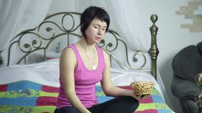 Athlete girl eating donut on a bed with pleasure, forbidden and junk food.  stock video