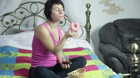 Athlete girl eating donut on a bed with pleasure, forbidden and junk food.  stock footage