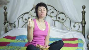 Athlete girl eating donut on a bed with pleasure, forbidden and junk food.  stock video footage