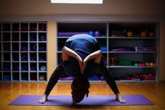 An athlete girl makes incredible yoga exercises in the gym. Royalty Free Stock Photos