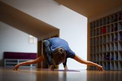 An athlete girl makes incredible yoga exercises in the gym. Stock Photos