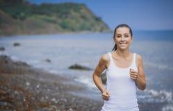Athlete girl on morning jog on the beach. Cute athlete on morning jog Stock Photo