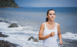 Athlete girl on morning jog on the beach Stock Images