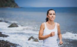 Athlete girl on morning jog on the beach. Cute athlete on morning jog Stock Images