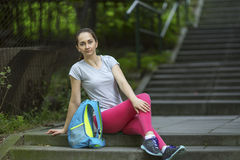 Athlete girl sitting on the stone stairs in the Park. Royalty Free Stock Photo