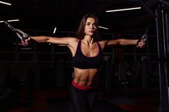 Athlete girl in sportswear working out and training her arms and shoulders with exercise machine in gym. Royalty Free Stock Photography