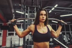 Athlete girl in sportswear working out and training her arms and shoulders with exercise machine in gym. Stock Photos