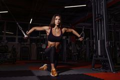 Athlete girl in sportswear working out and training her arms and shoulders with exercise machine in gym. Royalty Free Stock Images