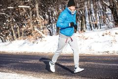 Athlete going for a run outdoor in snow, hardcore training and jogging Stock Photography
