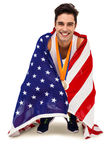 Athlete with gold medals around his neck wrapped in american flag. After victory on white background Stock Photography