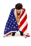 Athlete with gold medals around his neck wrapped in american flag. After victory on white background Royalty Free Stock Image