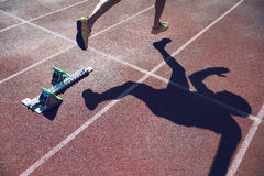 Athlete in Gold Shoes Sprinting Across Starting Line. Athlete in gold shoes sprinting from the starting blocks over the starting line of a race on a red running stock photography