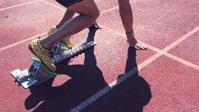 Athlete in Gold Shoes Sprinting Across Starting Line