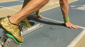 Athlete in Gold Shoes on Starting Blocks Slow Motion stock video
