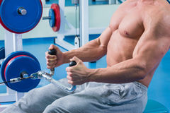 The athlete in the gym. Exhausting classes. Work on your body. Sophisticated power exercises Stock Photos