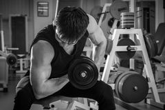 The athlete in the gym. Exhausting classes. Work on your body. Sophisticated power exercises. Photos for magazines, posters, backdrops and websites Stock Photos