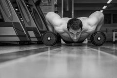 The athlete in the gym. Exhausting classes. Work on your body. Sophisticated power exercises. Photos for magazines, posters, backdrops and websites Royalty Free Stock Photography