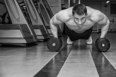 The athlete in the gym. Exhausting classes. Work on your body. Sophisticated power exercises. Photos for magazines, posters, backdrops and websites Stock Images