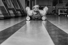 The athlete in the gym. Exhausting classes. Work on your body. Sophisticated power exercises. Photos for magazines, posters, backdrops and websites Royalty Free Stock Photos