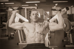 The athlete in the gym. Exhausting classes. Work on your body. Sophisticated power exercises. Photos for magazines, posters, backdrops and websites Stock Photography