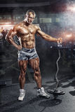 Athlete in the gym training with barbell. Bodybuilder male athlete in the gym training with bar Stock Image