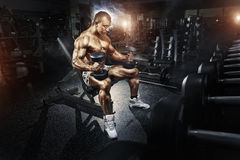 Athlete in the gym training with dumbbells. Bodybuilder male athlete in the gym training with dumbbells Royalty Free Stock Photography