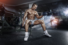 Athlete in the gym training with dumbbells Royalty Free Stock Photo