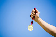 Athlete hand holding gold medal after victory Stock Photography