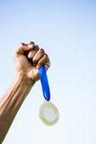 Athlete hand holding gold medal after victory. Determined relay athlete running with baton running track stock images