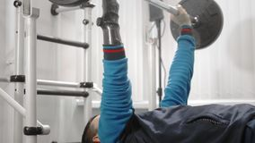 An athlete without a hand raises the barbell while lying down. Holds the bar with a professional sports hand prosthesis