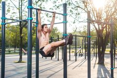 Athlete hanging on fitness station performing legs raises. Core cross training working out abs muscles.  stock images