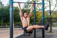 Athlete hanging on fitness station performing legs raises. Core cross training working out abs muscles.  royalty free stock photography