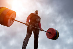 Athlete have difficulty holding a heavy barbell. Against the sky Royalty Free Stock Photo