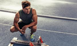Sprinter sitting beside a starting block on running track Royalty Free Stock Photography