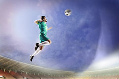 Athlete heading soccer ball in stadium. At game royalty free stock image
