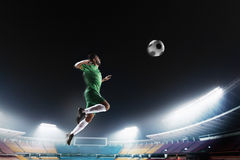Athlete heading soccer ball in stadium. At game stock photo
