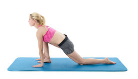 Woman exercising. Attractive blonde woman wearing pink sports bra and gray shorts kneeling on one knee (in a somewhat contorted position) on a blue rubber mat stock photography