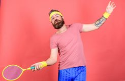 Athlete hipster hold tennis racket in hand red background. Man bearded hipster wear sport outfit. Having fun. Tennis. Active leisure. Tennis player vintage stock image