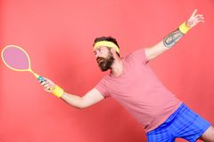 Athlete hipster hold tennis racket in hand red background. Man bearded hipster wear sport outfit. Tennis player beginner. Retro fashion. Concentrated on tennis royalty free stock photo