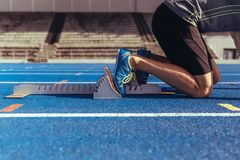 Sprinter resting his feet on starting block on running track. Athlete on his mark ready to sprint on an all-weather running track. Runner using a starting block Stock Photo