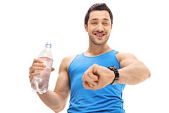 Athlete holding a bottle of water and looking at his watch Stock Photo