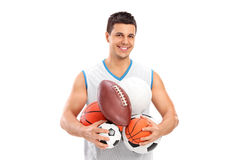 Athlete holding a bunch of different kinds of balls Stock Photo