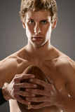 Athlete holding a football Stock Image