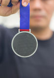 Athlete Holding Generic Gold Medal With Ribbon On His Hand. Royalty Free Stock Photography