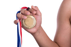 Athlete holding gold medal with ribbon on his hand Royalty Free Stock Images