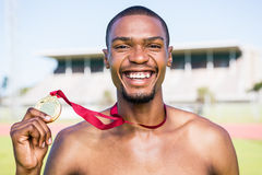 Athlete holding gold medal after victory Stock Photos